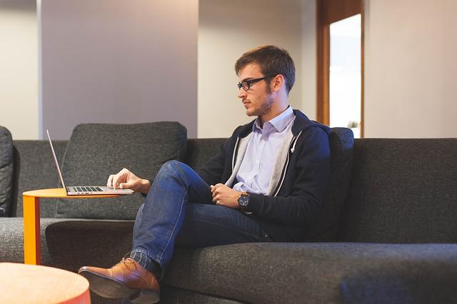 Mann i sofa med datamaskin