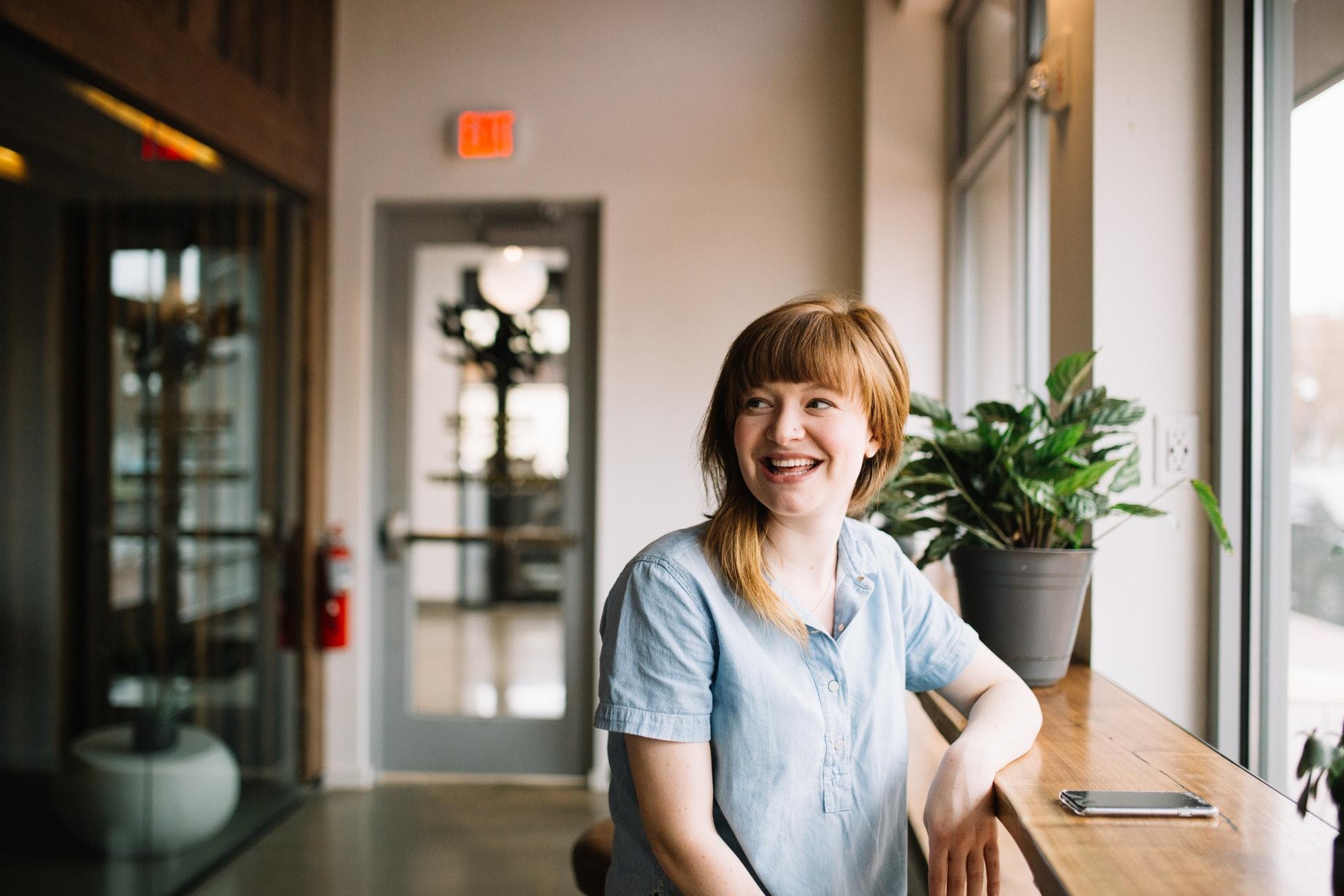 Glad kvinne som sitter ved et kafevindu